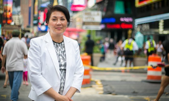 Judy Chen, who has been harassed in Flushing, Queens, because she practices Falun Gong, a spiritual practice based on principles of truthfulness, compassion, and tolerance, poses on Times Square, Manhattan, New York, on June 25, 2014. (Benjamin Chasteen/Epoch Times)