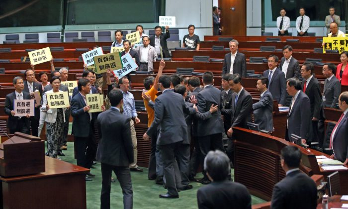 """Over 20 pan-democratic LegCo members collectively walk out to protest against Chief Executive Leung Chun-ying during Question and Answer Session in LegCo chamber on July 3, 2014. They are holding banners demanding for """"Genuine Universal Suffrage, No Screening."""" (C.S. Poon/Epoch Times)"""