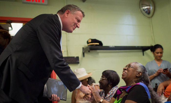 Mayor Bill de Blasio shakes hands with pulbic housing residents prior to announcing a set of crime reduction initiatives at the Wagner Houses in East Harlem in New York on July 8, 2014. (Ivan Pentchoukov/Epoch Times)