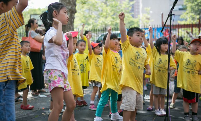 """Young children learn dance moves from Corey Baker, a dancer in """"Spill,"""" an outdoor production created specifically for playgrounds, at Columbus Park in Chinatown, Manhattan, on July, 8, 2014. (Benjamin Chasteen/Epoch Times)"""