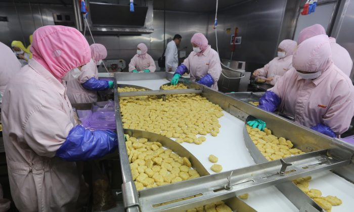 Workers produce food at the Shanghai Husi Food Co., part of the OSI Group, a U.S. food processor, in Shanghai on July 20, 2014. Shanghai city officials have shut down the plant for producing fast-food products using expired meat. (STR/AFP/Getty Images)