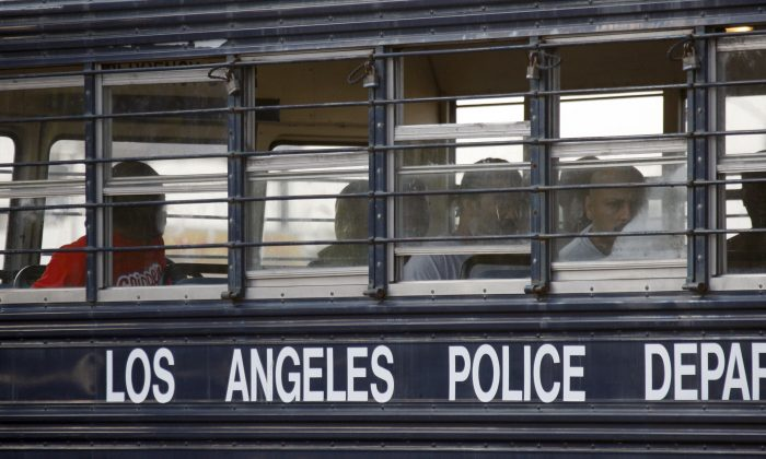 Suspected gang members sit in a bus after their arrest by members of a task force from the Los Angeles police department and the FBI in Los Angeles on May 19, 2011. (AP Photo/Nick Ut)