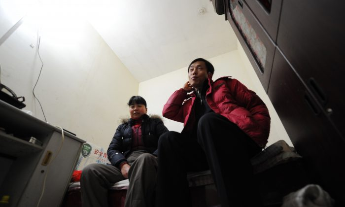 """Chinese migrant workers sit in their tiny room, three stories down in a dimly lit air raid shelter in Beijing. These workers belong to what Beijing citizens are now referring to as the """"rat tribe."""" (Peter Parks/AFP/Getty Images)"""