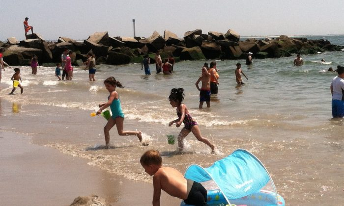 Children play at the Coney Island beach in Brooklyn on Wednesday, July, 23, 2014. After 10 year-old Takara McDuffy drowned on Tuesday evening at the beach, Brooklyn borough president Eric Adams announced efforts to pass legislation requiring water safety education in all city public schools. (Annie Wu/Epoch Times)