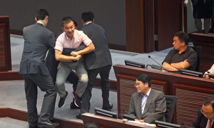 LegCo member Raymond Chan Chi-chuen is carried out by security guards after protesting the government reports that he feels do not honestly reflect Hong Kong citizens' demand for civic nomination on July 15, 2014. (Epoch Times)