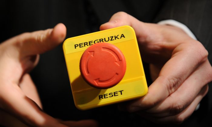 """An assistant shows the block with a red button marked """"reset"""" in English and """"overload"""" in Russian that U.S. Secretary of State Hillary Clinton handed to Russian Foreign Minister Sergei Lavrov during a meeting in Geneva on March 6, 2009. (Fabrice Coffrini/AFP/Getty Images)"""