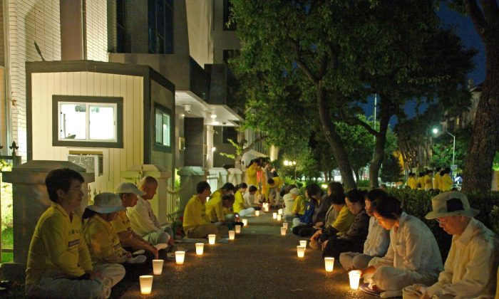 Practitioners hold candles in remembrance of the innocent Falun Dafa practitioners killed because of their faith and for their organs. (Robin Kemker/The Epoch Times)