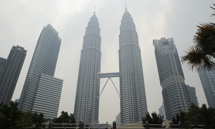Malaysia's landmark Petronas Twin Towers (C) are covered with light haze in Kuala Lumpur on July 23, 2013. An incident involving diplomatic immunity has caused an uproar in both Malaysia and New Zealand. (Mohd Rasfan/AFP/Getty Images)
