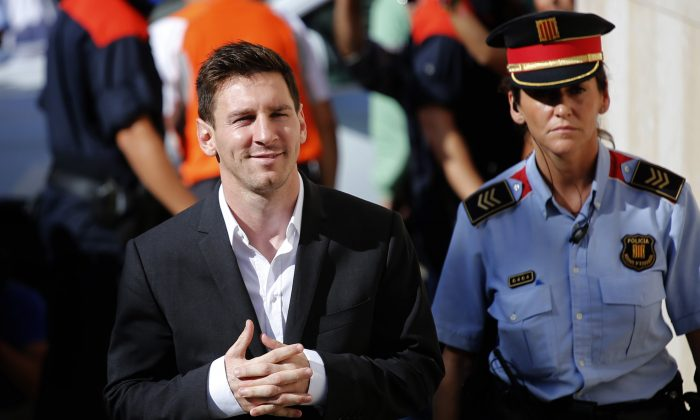 FC Barcelona star Lionel Messi, left, arrives at a court to answer questions in a tax fraud case in Gava, near Barcelona, Spain, on Sept. 27, 2013. (AP Photo/Emilio Morenatti)