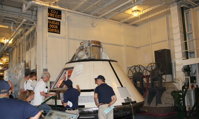 "Visitors look at the lunar module or ""capsule CM-011A"" during the ""Splashdown 45"" event aboard the USS Hornet in Alameda, Calif., on July 26. (Steve Ispas/Epoch Times)"