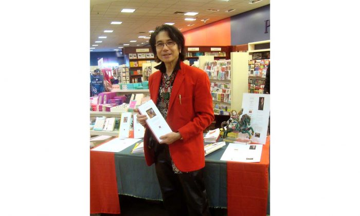 """Reuben Tom Kee holds his book """"Ode to China: Sagacity!"""" at a book signing at Chapters book store in Ottawa in 2013. (Courtesy of Reuben Tom Kee)"""
