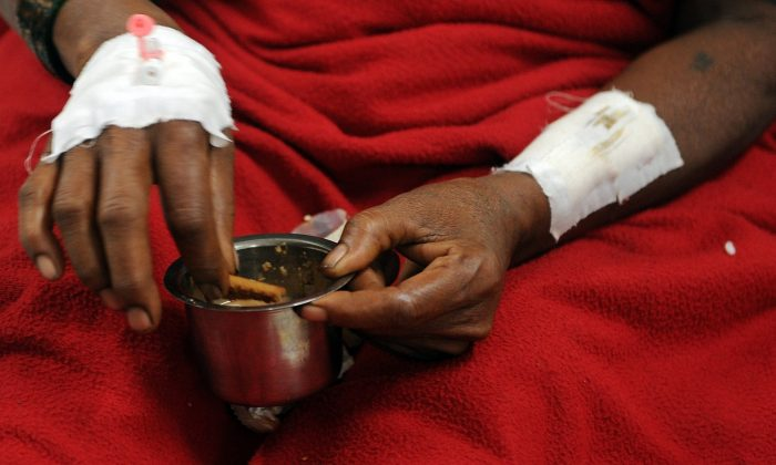 Indian woman, Meenabai Lembe, survivor of the landslide at Malin village in Pune district in the western state of Maharashtra, dips a biscuit into her tea as she recuperates at a government hospital in Manchar on July 31, 2014. Rescuers battled through heavy rains in a desperate search for victims of a landslide in western India that buried dozens of homes, with fears the death toll could reach 150. (Indranil Mukherjee/AFP/Getty Images)