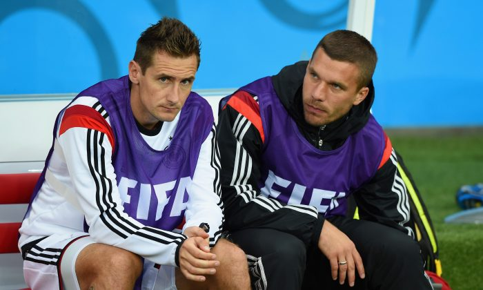 Miroslav Klose (L) and Lukas Podolski of Germany look on from the bench during the 2014 FIFA World Cup Brazil Round of 16 match between Germany and Algeria at Estadio Beira-Rio on June 30, 2014 in Porto Alegre, Brazil. (Matthias Hangst/Getty Images)