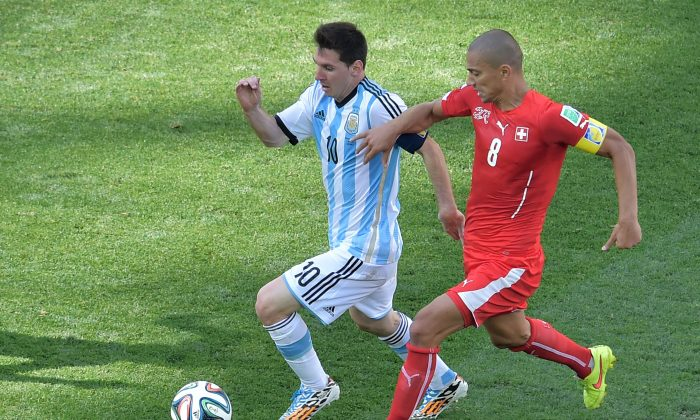 Argentina's forward and captain Lionel Messi (L) is challenged by Switzerland's midfielder and captain Goekhan Inler during the second half of a Round of 16 football match between Argentina and Switzerland at Corinthians Arena in Sao Paulo during the 2014 FIFA World Cup on July 1, 2014. (Gabriel Bouys/AFP/Getty Images)