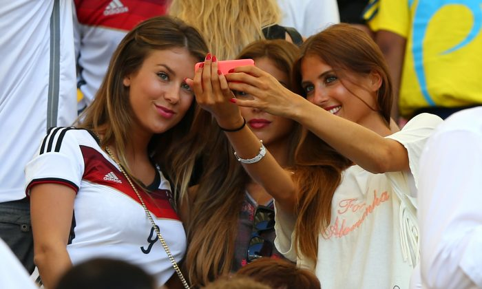 (L-R) Montana Yorke, girlfriend of Andre Schuerrle of Germany, Ann-Kathrin Brommel, girlfriend of Mario Gotze of Germany, and Cathy Fischer, girlfriend of Mats Hummels of Germany, take a selfie during the 2014 FIFA World Cup Brazil Quarter Final match between France and Germany at Maracana on July 4, 2014 in Rio de Janeiro, Brazil. (Martin Rose/Getty Images)