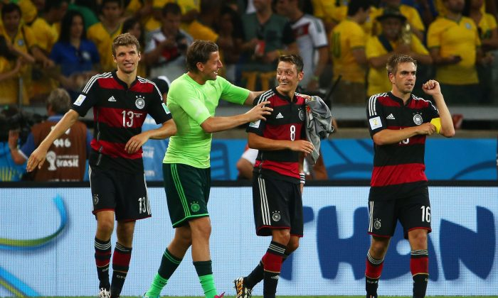 (L-R) Thomas Mueller, Manuel Neuer, Mesut Oezil and Philipp Lahm of Germany celebrate a 7-1 victory over Brazil during the 2014 FIFA World Cup Brazil Semi Final match between Brazil and Germany at Estadio Mineirao on July 8, 2014 in Belo Horizonte, Brazil. (Robert Cianflone/Getty Images)