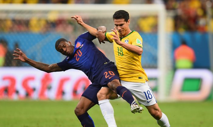 Georginio Wijnaldum of the Netherlands and Hernanes of Brazil compete for the ball during the 2014 FIFA World Cup Brazil Third Place Playoff match between Brazil and the Netherlands at Estadio Nacional on July 12, 2014 in Brasilia, Brazil. (Jamie McDonald/Getty Images)