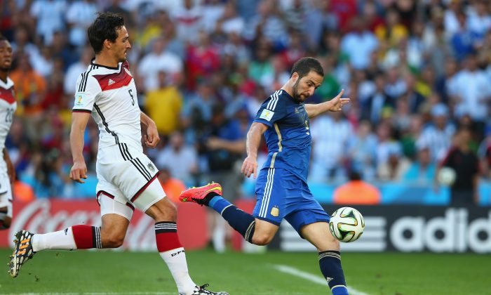 Gonzalo Higuain of Argentina shoots wide as Mats Hummels of Germany defends during the 2014 FIFA World Cup Brazil Final match between Germany and Argentina at Maracana on July 13, 2014 in Rio de Janeiro, Brazil. (Photo by Julian Finney/Getty Images)