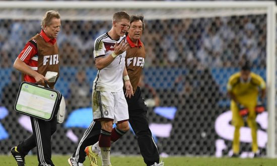 d5355508c Germany s midfielder Bastian Schweinsteiger (C) is escorted of the pitch by  medics after clashing