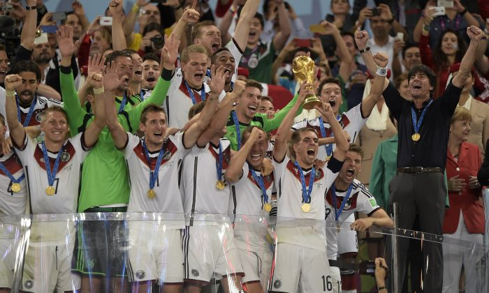 Germany's defender and captain Philipp Lahm (front-R) holds the World Cup trophy as he celebrates with his teammates after winning the final football match between Germany and Argentina for the FIFA World Cup at The Maracana Stadium in Rio de Janeiro on July 13, 2014. (JUAN MABROMATA/AFP/Getty Images)
