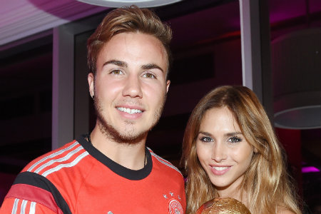 Goalscorer Mario Gotze of Germany and girlfriend Ann-Kathrin Brommel pose with the World Cup trophy as he celebrates with teammates at a party, after winning the 2014 FIFA World Cup Brazil Final match against Argentina, at Sheraton Hotel on July 13, 2014 in Rio de Janeiro, Brazil. (Photo by Markus Gilliar - Pool/Getty Images)