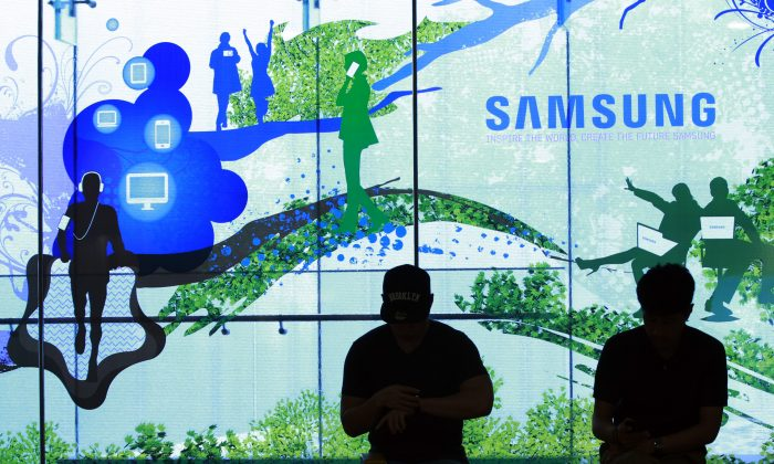 People stand in front of a Samsung Electronics Co's showroom in Seoul, South Korea, Thursday, July 31, 2014. Samsung Electronics Co. reported a bigger-than-expected fall in second quarter profit on Thursday and said it was uncertain if earnings from its handset business would improve in the current quarter.(AP Photo/Ahn Young-joon)