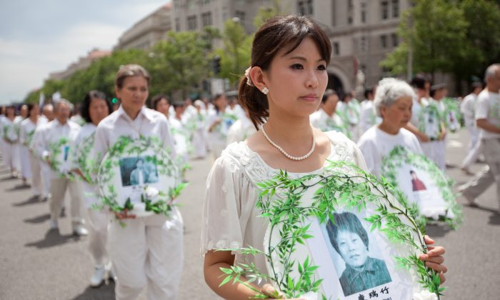 Marching Falun Gong practitioners hold photos of victims of the persecution during a parade in Washington, D.C., on July 18, 2011. (Epoch Times)