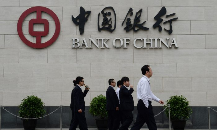 Bank workers walk outside the headquarters of the Bank of China in the Xidan District of Beijing on May 8, 2013. The state-owned Bank of China was accused of money laundering by Party mouthpiece Chinese Central Television on July 9. (Mark Ralston/AFP/Getty Images)