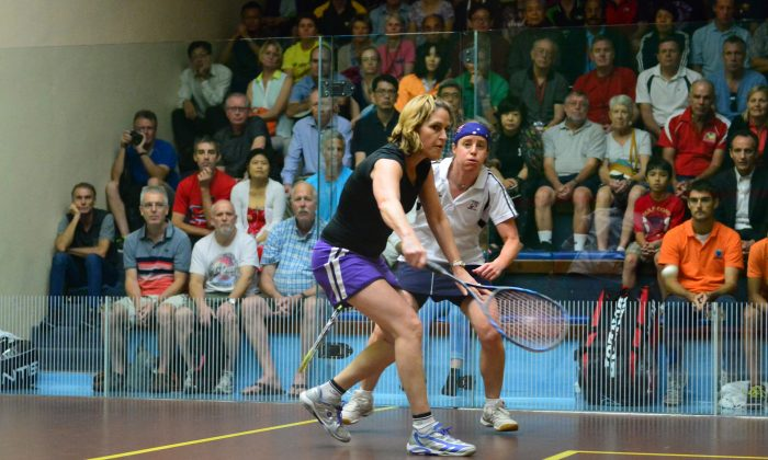 Five times Squash World Champion Sarah Fitz-Gerald of Australia (on strike) on her way to winning her first World Masters Title playing in the Ladies 45+ event against fellow Australian Sarah Nelson at the Hong Kong Squash Centre on Friday July 11, 2014. (Bill Cox/Epoch Times)
