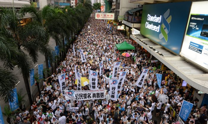 A mass of protesters march through Hong Kong's streets in support of universal suffrage on July 1. The march has become a tradition since 2003, when communist authorities in China attempted to pass a controversial anti-sedition law. (Song Xianglong/Epoch Times)