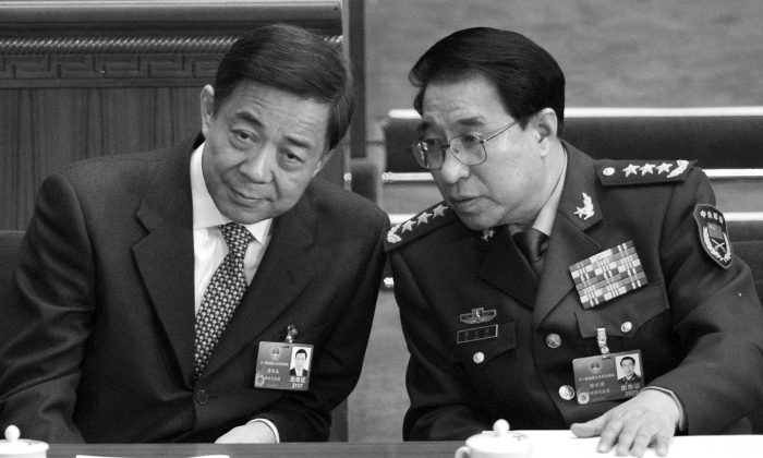 Disgraced Politburo member Bo Xilai (L) talks to Xu Caihou at the National People's Congress on March 5, 2012. A little over a month later, Bo Xilai was purged; on July 2, 2014, Xu was also expelled fro the Chinese Communist Party. (Liu Jin/AFP/Getty Images)