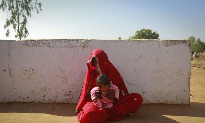 Krishna, 14, sits with her four-month-old baby outside her house in a village in the northwestern state of Rajasthan, India, Jan. 21, 2013. Krishna was married to her husband Gopal when she was 11 and he was 13. Canada is contributing $20 million over two years to UNICEF toward ending child marriage in six countries. (REUTERS/Danish Siddiqui)