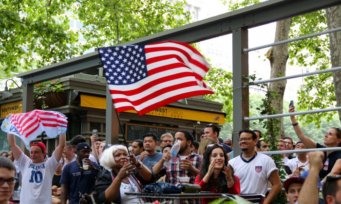 Fans prepare to watch the World Cup soccer game between the United States and Belgium at Bryant Park in Manhattan on Tuesday. (Allen Xie/Epoch Times)