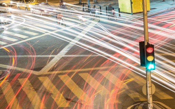 Green drivers swiftly pass a traffic light. *Shutterstock
