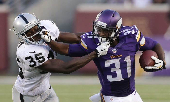 Minnesota Vikings running back Jerick McKinnon (31) stiff-arms Oakland Raiders defensive back Chimdi Chekwa (35) in the first half during a exhibition NFL football game in Minneapolis, Friday, Aug. 8, 2014. (AP Photo/Jim Mone)