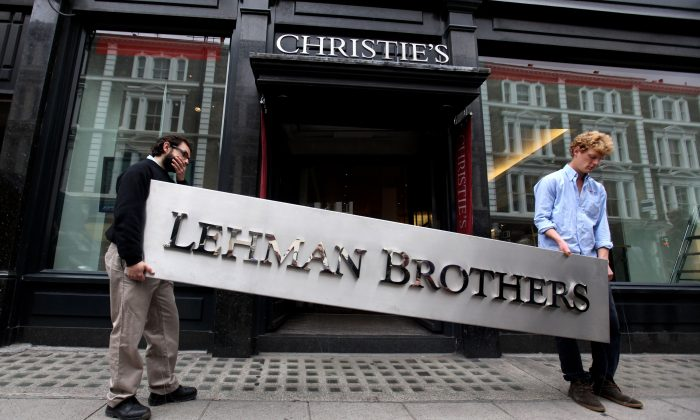 Two employees of Christie's auction house maneuver the corporate logo of the collapsed investment bank Lehman Brothers in London, England, on Sept. 24, 2010. (Oli Scarff/Getty Images)