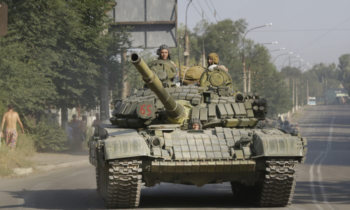 Pro-Russia rebels ride on a tank in the town of Krasnodon, eastern Ukraine, Aug. 17, 2014. On Thursday the presence of invading Russian forces inside Ukraine was confirmed. (AP Photo/Sergei Grits)
