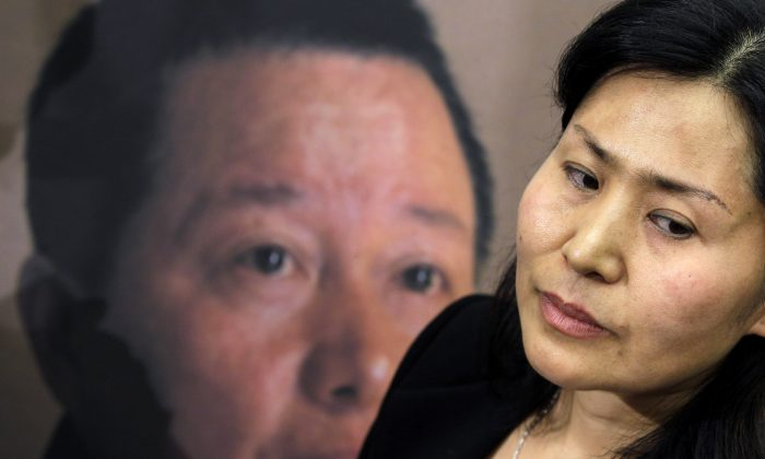 Geng He, wife of disappeared Chinese human rights lawyer Gao Zhisheng, seen on a poster at rear, on Capitol Hill in Washington, Tuesday, Jan. 18, 2011. (AP Photo/Charles Dharapak)