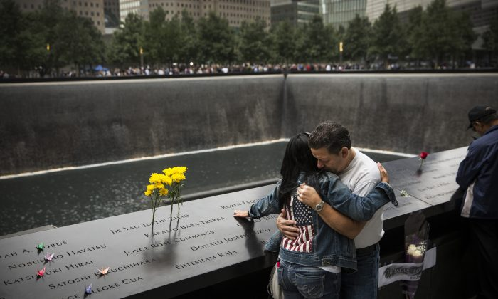Eileen Esquilin hugs her husband, Joe Irizarry, while mourning the loss of her brother, Ruben Esquilin Jr., during Sept. 11 memorial observances in New York City on Thursday. (Andrew Burton/Getty Images)