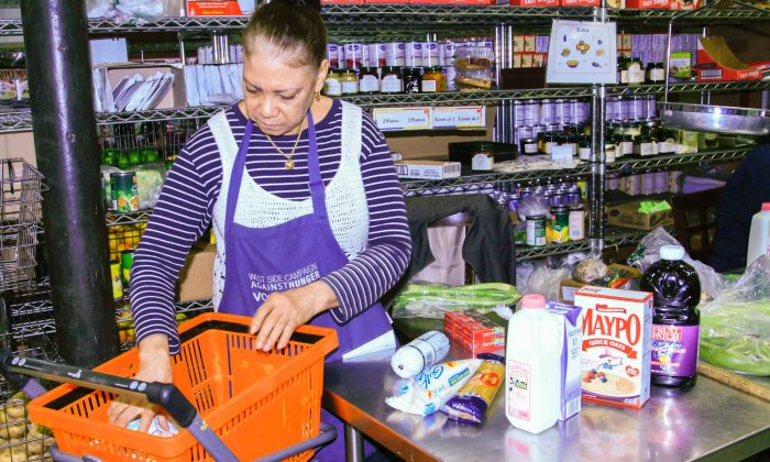 A cashier looks over groceries at West Side Campaign Against Hunger food bank in the Upper West Side on Monday, Sept. 18, 2014. (Shannon Liao/Epoch Times)