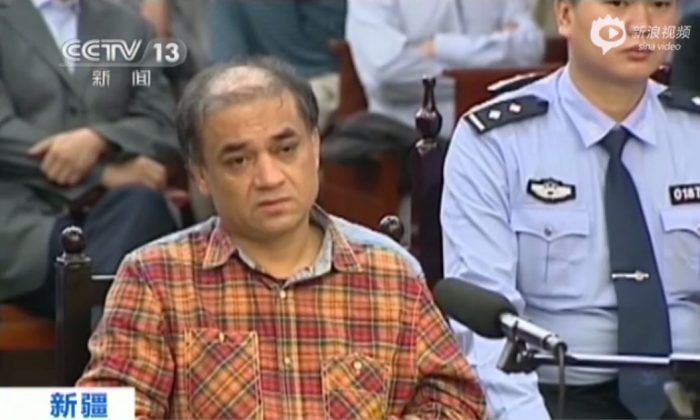 """Uyghur university professor Ilham Tohti sits in the Urumqi People's Intermediate Court in western China's Xinjiang, on Sept. 23, 2014. He was sentenced life in prison for """"separatism"""" by a Xinjiang court on Sept. 23, 2014. (Screenshot/China Central Television)"""
