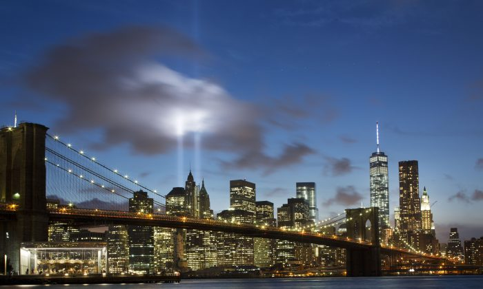 The Tribute in Light rises behind the Brooklyn Bridge at the World Trade Center complex in New York on Sept. 10, 2014.  (AP Photo/Mark Lennihan)