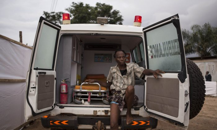 "In this photo taken on Wednesday, Sept. 24, 2014, a woman suspected of suffering from the Ebola virus sits in an ambulance in Kenema, Sierra Leone. Sierra Leone restricted travel Thursday, Sept. 25, 2014 in three more ""hotspots"" of Ebola where more than 1 million people live, meaning about a third of the country's population is now under quarantine. Sierra Leone is one of the hardest hit countries in the Ebola outbreak sweeping West Africa that is believed to have killed more than 2,900 people, according to World Health Organization tolls published Thursday. (AP Photo/ Tanya Bindra)"