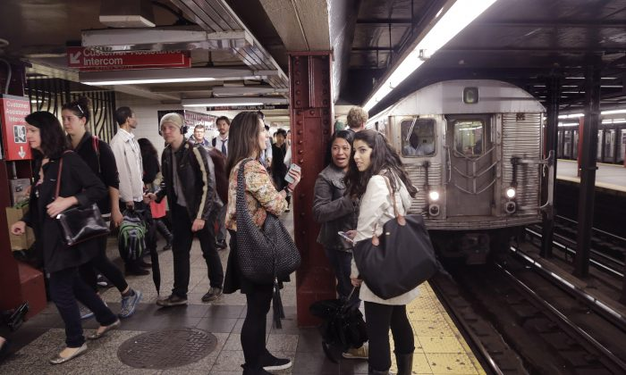 Subway passengers wait on a platform, Thursday, Sept. 25, 2014 in New York. (AP Photo/Mark Lennihan)