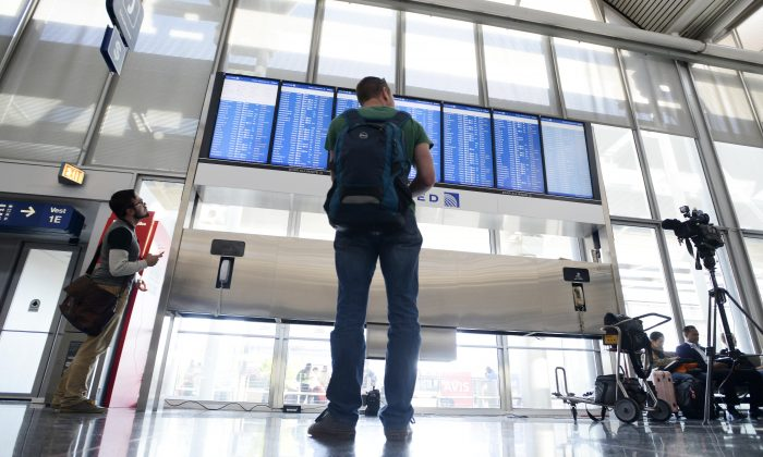 Dennis McCormack of Rockaway, N.J. checks the departure board only to find out that his flight to Newark, N.J. has been canceled at O'Hare International Airport in Chicago, Friday, Sept. 26, 2014. (AP Photo/Paul Beaty)