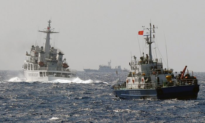 This picture taken from a Vietnam Coast Guard ship on May 14, 2014 shows a China Coast Guard ship (L) blocking the way of a Vietnam Coast Guard ship near to the site of a Chinese drilling oil rig (R, background) being installed at the disputed water in the South China Sea off Vietnam's central coast. (Hoang Dinh Nam/AFP/Getty Images)