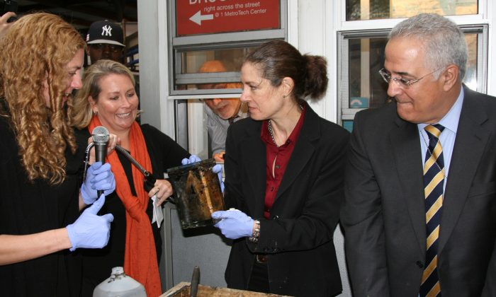 Conservator Toya Dubin (C) presents the glass canister in Brooklyn, N.Y., on Oct. 1, 2014. (Shannon Liao/Epoch Times)