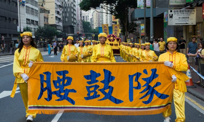 Falun Gong practitioners along with people from the global center for quitting the Chinese Party, march in a parade down the streets in Hong Kong to protest China's National Day on Oct. 1, 2014. (Benjamin Chasteen/Epoch Times)