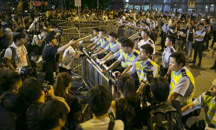 Protesters confront police overnight outside the legislative government complex on October 2, 2014 in Hong Kong. Thousands of pro democracy supporters continue to occupy the streets surrounding Hong Kong's financial district. The protests are a new geopolitical threat affecting financial market sentiment. (Paula Bronstein/Getty Images)