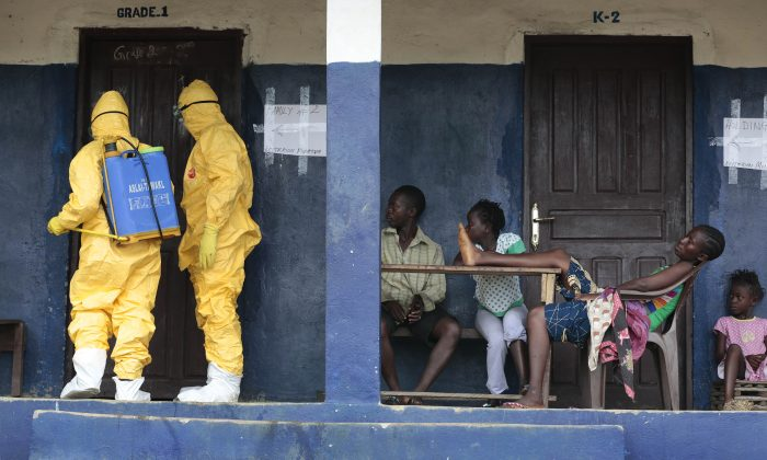 Residents of the village of Freeman Reserve, about 30 miles north of Monrovia, Liberia, watch members of District 13 ambulance service disinfect a room as they pick up six suspected Ebola sufferers that had been quarantined, Tuesday Sept. 30, 2014. Six months into the world's worst-ever Ebola outbreak, and the first to happen in an unprepared West Africa, the gap between what has been sent by other countries and private groups and what is desperately needed is huge. Even as countries try to marshal more resources to close the gap, those needs threaten to become much greater, and possibly even insurmountable. (AP Photo/Jerome Delay)